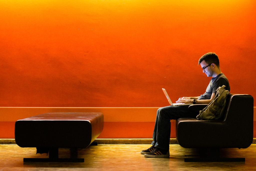 Jon Wallace writing stuff on a white laptop in an orange room.